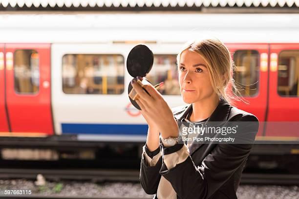 Businesswoman powdering nose, London Underground, UK