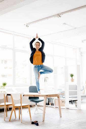 Businesswoman practising yoga on desk in a loft - gettyimageskorea