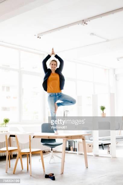 Businesswoman practising yoga on desk in a loft