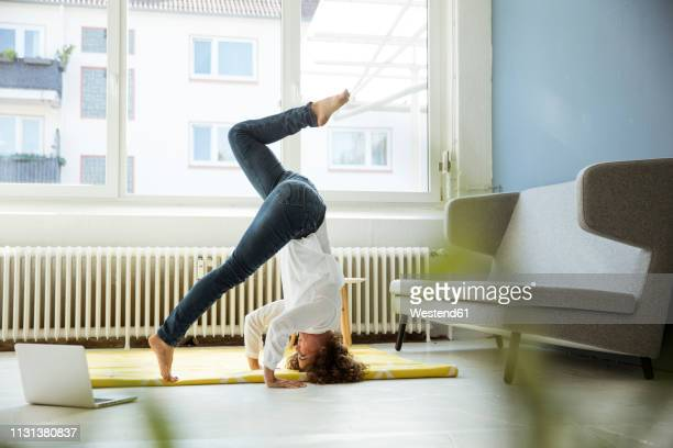 businesswoman practising yoga on the floor - auf den kopf gestellt stock-fotos und bilder