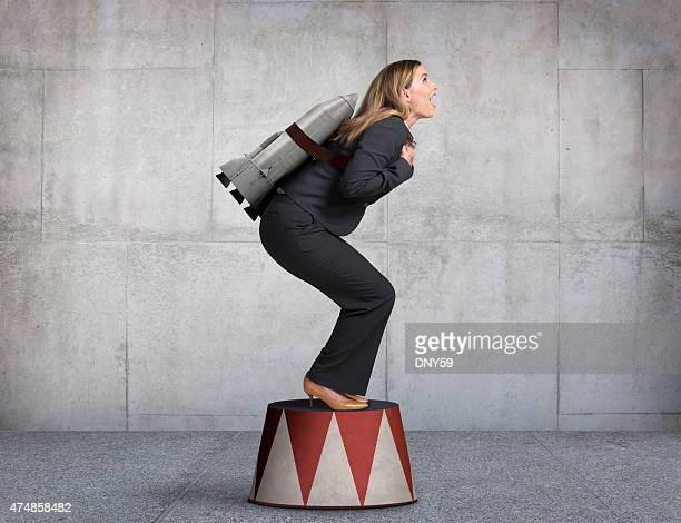 Businesswoman Preparing For Takeoff On Circus Pedestal