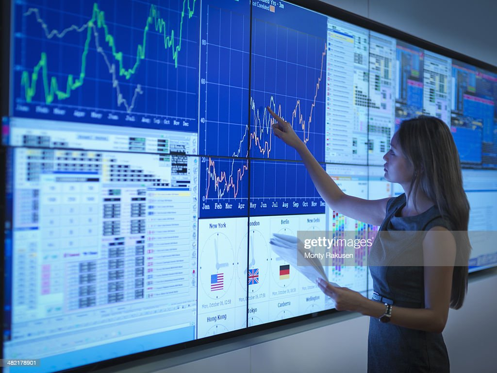 Businesswoman preparing presentation on graphical screens : Stock Photo