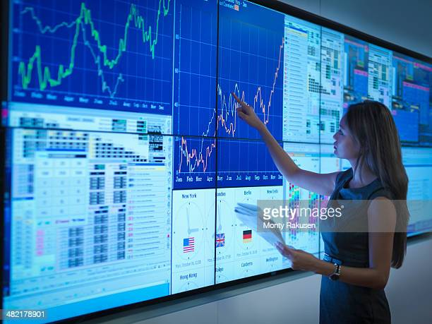 Businesswoman preparing presentation on graphical screens