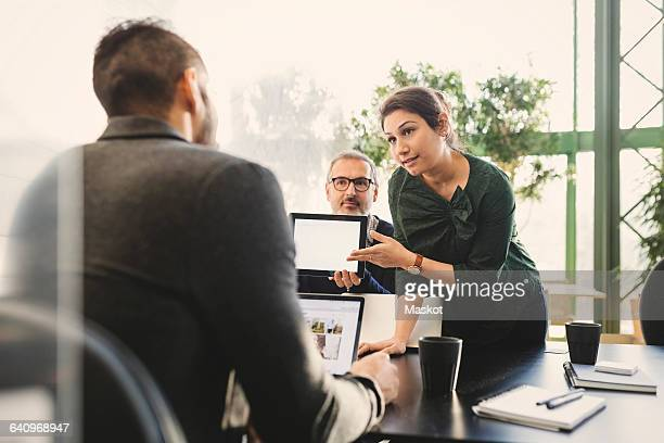 Businesswoman presenting her ideas on digital tablet to manager in office