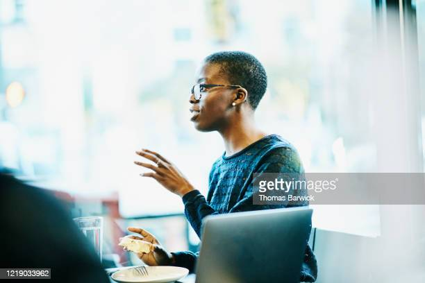businesswoman presenting project to client during lunch meeting in restaurant - gesturing stock pictures, royalty-free photos & images