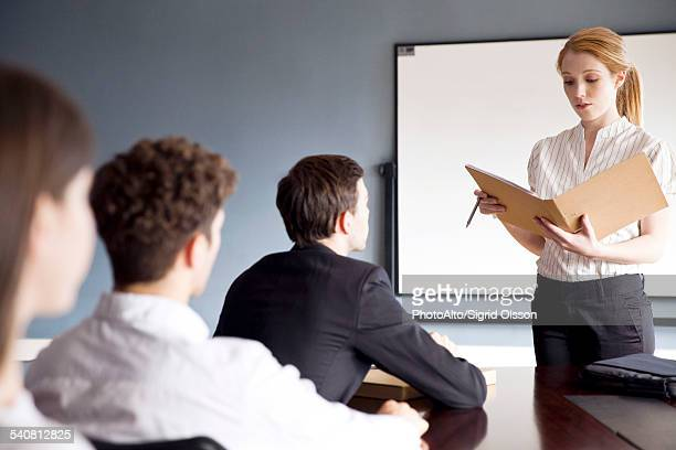 Businesswoman presenting report at corporate meeting
