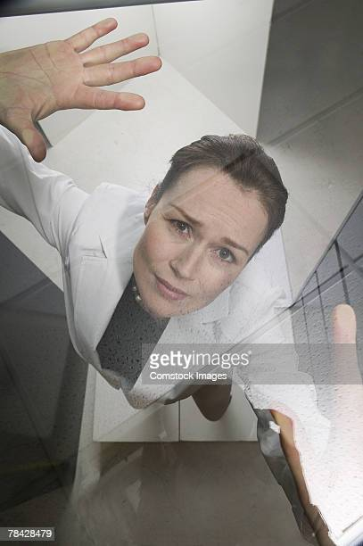 Businesswoman pressing against glass ceiling