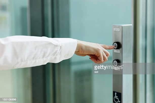 Businesswoman pressing button for elevator
