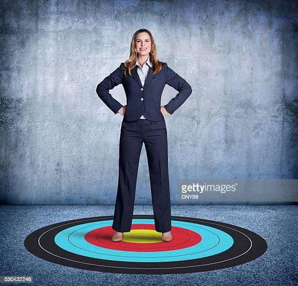 Mujer de negocios de pie en el piso superior, se enorgullece de su objetivo.