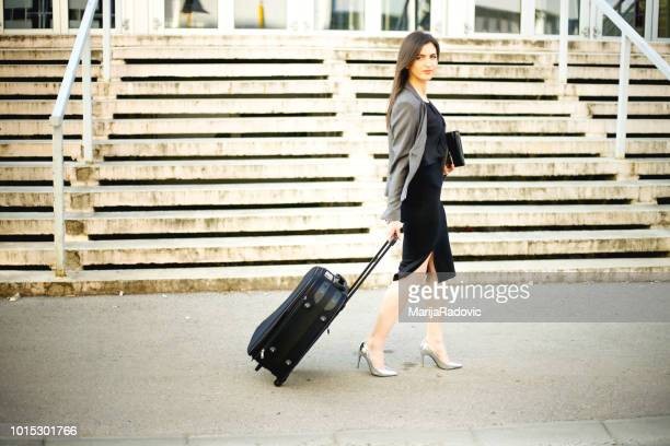Businesswoman pulling a suitcase in city