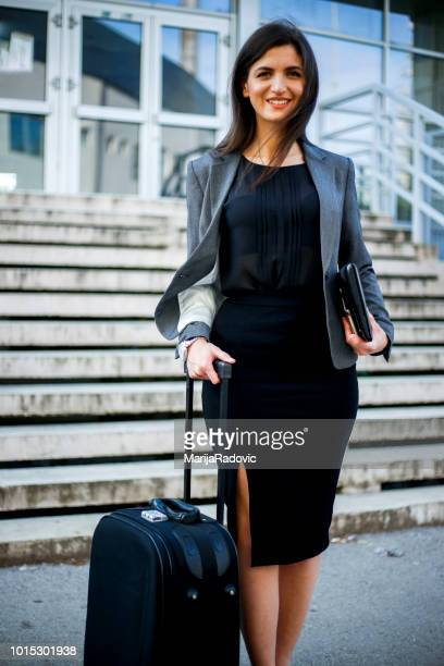 businesswoman pulling a suitcase in city - black skirt stock pictures, royalty-free photos & images