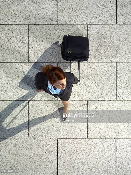 A businesswoman pulling a suitcase