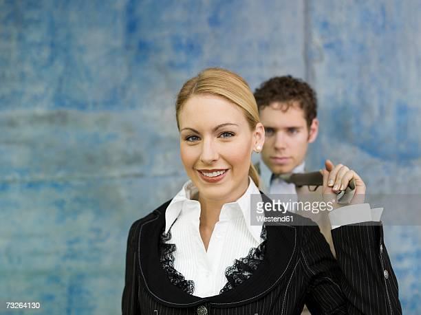 Businesswoman pulling businessman's tie, smiling