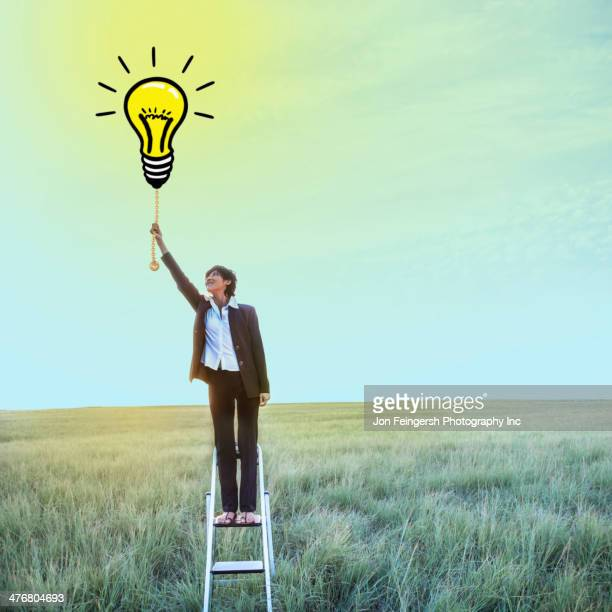 Businesswoman pulling chain on light bulb illustration