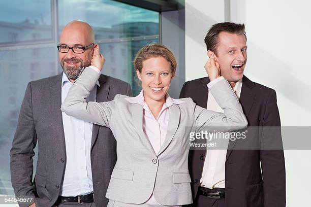 Businesswoman pulling ears of colleagues