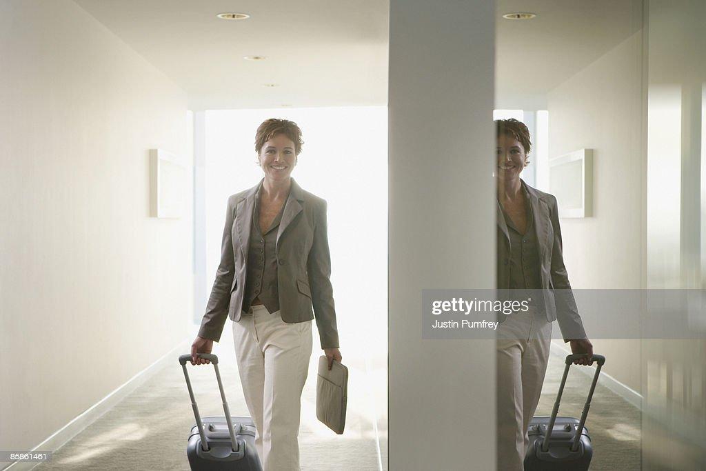 Businesswoman pulling luggage in corridor : Stock-Foto