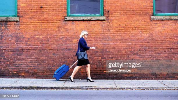 Businesswoman pulling suitcase down sidewalk in city.