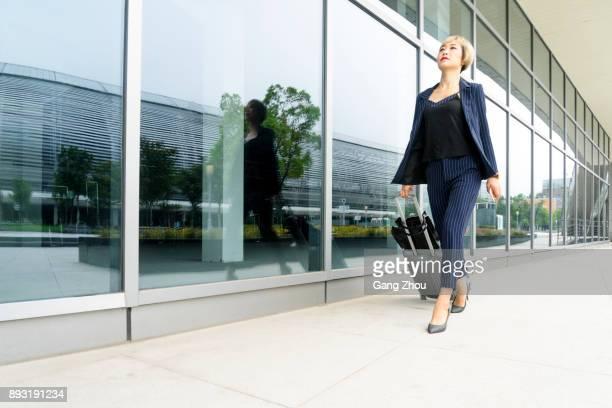 Geschäftsfrau ziehen Koffer auf Rädern vor Flughafen