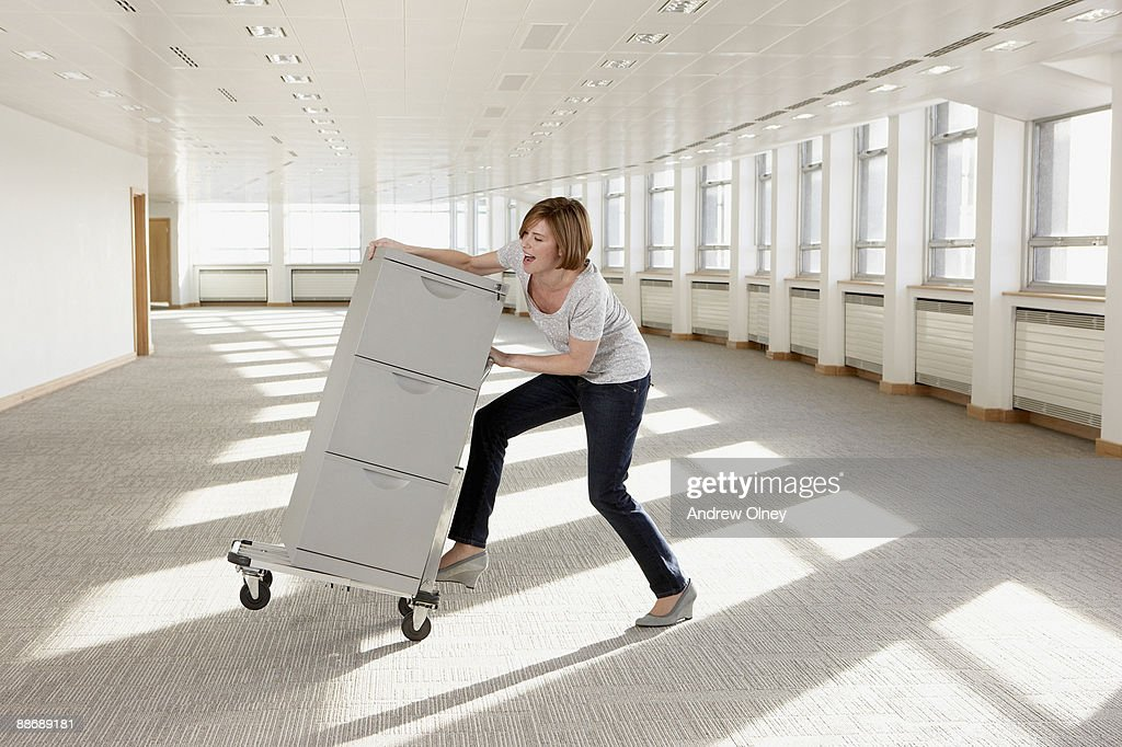 Businesswoman pushing filing cabinet on hand-truck : Stock Photo