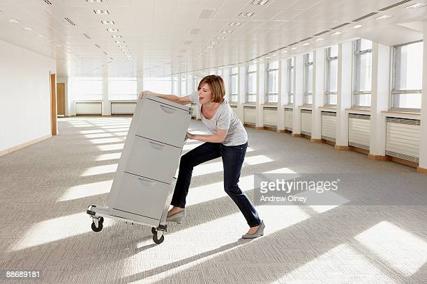 Businesswoman pushing filing cabinet on hand-truck