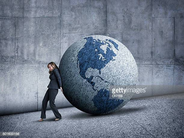 businesswoman pushing globe uphill - uphill stock pictures, royalty-free photos & images