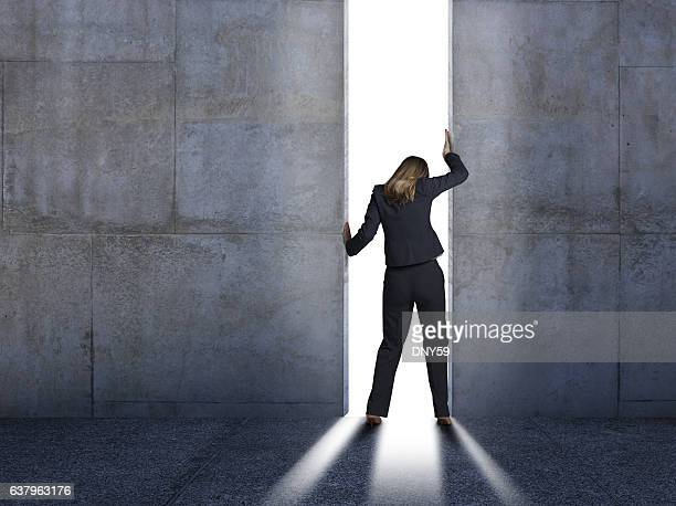 businesswoman pushing open concrete walls - openmaken stockfoto's en -beelden