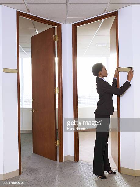 businesswoman putting nameplate on wall in empty office, side view - nameplate stock pictures, royalty-free photos & images