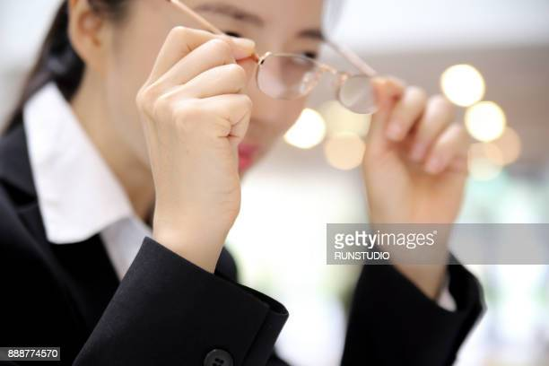 Businesswoman putting on eyeglasses