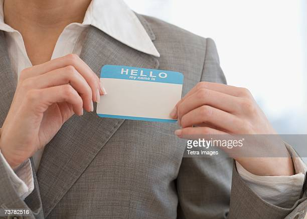 Businesswoman putting on Hello My Name Is sticker