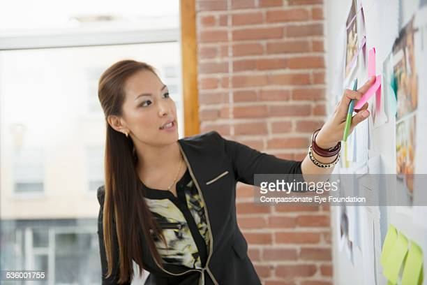 Businesswoman putting sticky note on wall