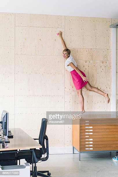 Businesswoman putting sticky note on wooden wall
