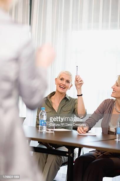 Businesswoman raising hand in meeting