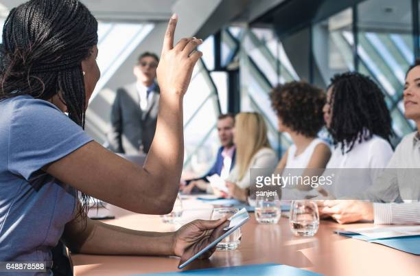 Businesswoman Raising Hand in The Middle of a Meeting