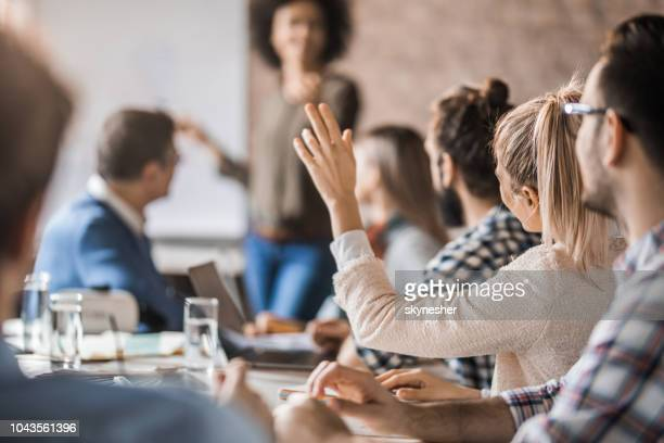 businesswoman raising her hand to ask a question on a business meeting in the office. - q&a stock pictures, royalty-free photos & images