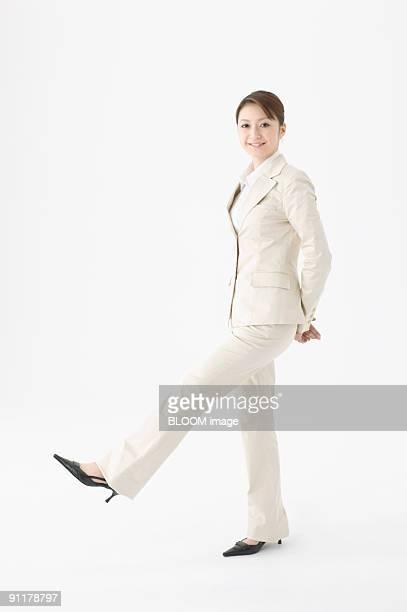 Businesswoman raising leg