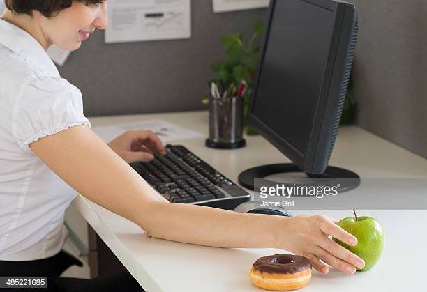 Businesswoman reaching for apple