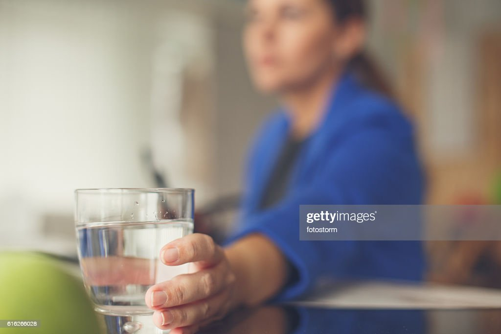 Businesswoman reaching for glass of water : Stock Photo