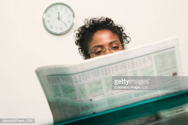 businesswoman reading a newspaper - delen begrippen stockfoto's en -beelden
