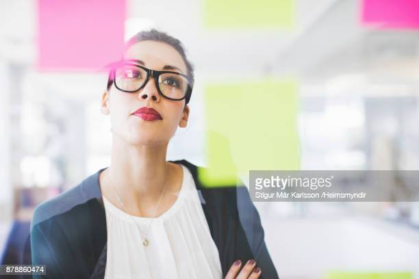 businesswoman reading adhesive notes on glass wall - to do list stock pictures, royalty-free photos & images