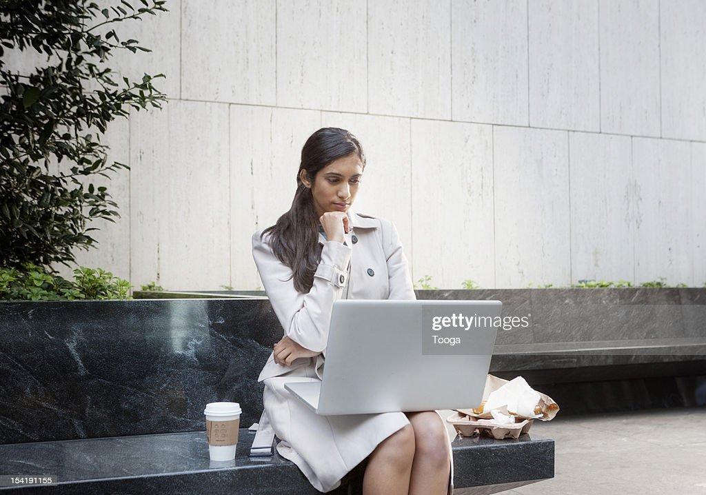 Businesswoman reading article on internet : Bildbanksbilder