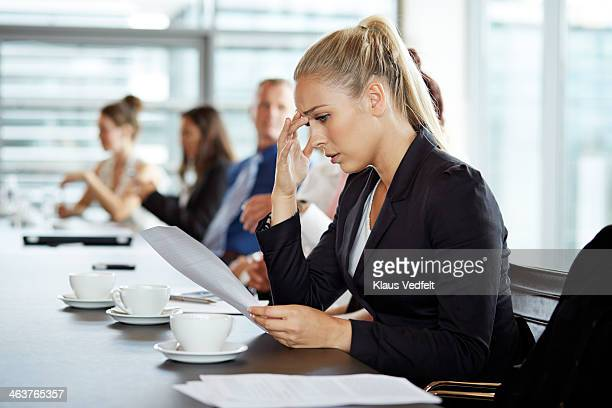 Businesswoman reading bad news from papers