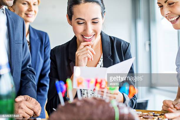 businesswoman reading birthday card in office - birthday card stock pictures, royalty-free photos & images