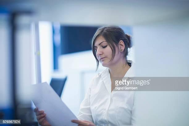 businesswoman reading document in office, freiburg, baden-w��rttemberg, germany - sigrid gombert fotografías e imágenes de stock
