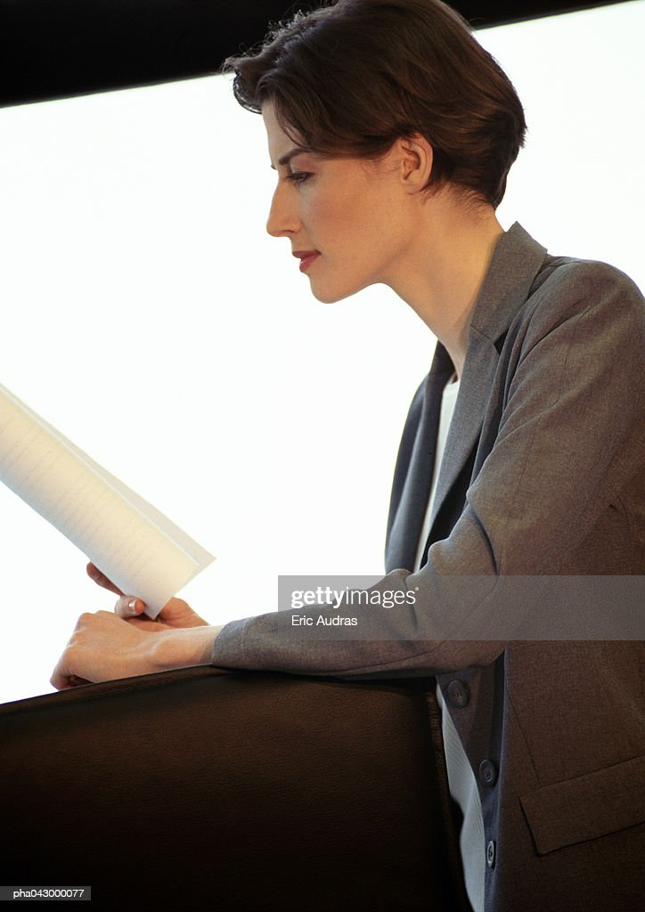 Businesswoman reading document, side view : Stockfoto