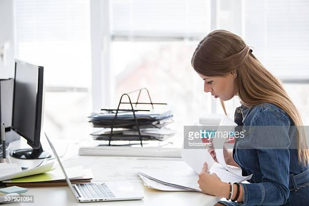 Lectura de los documentos de empresaria en escritorio de oficina