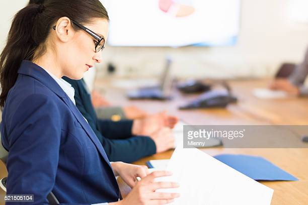 Businesswoman reading documents in meeting room