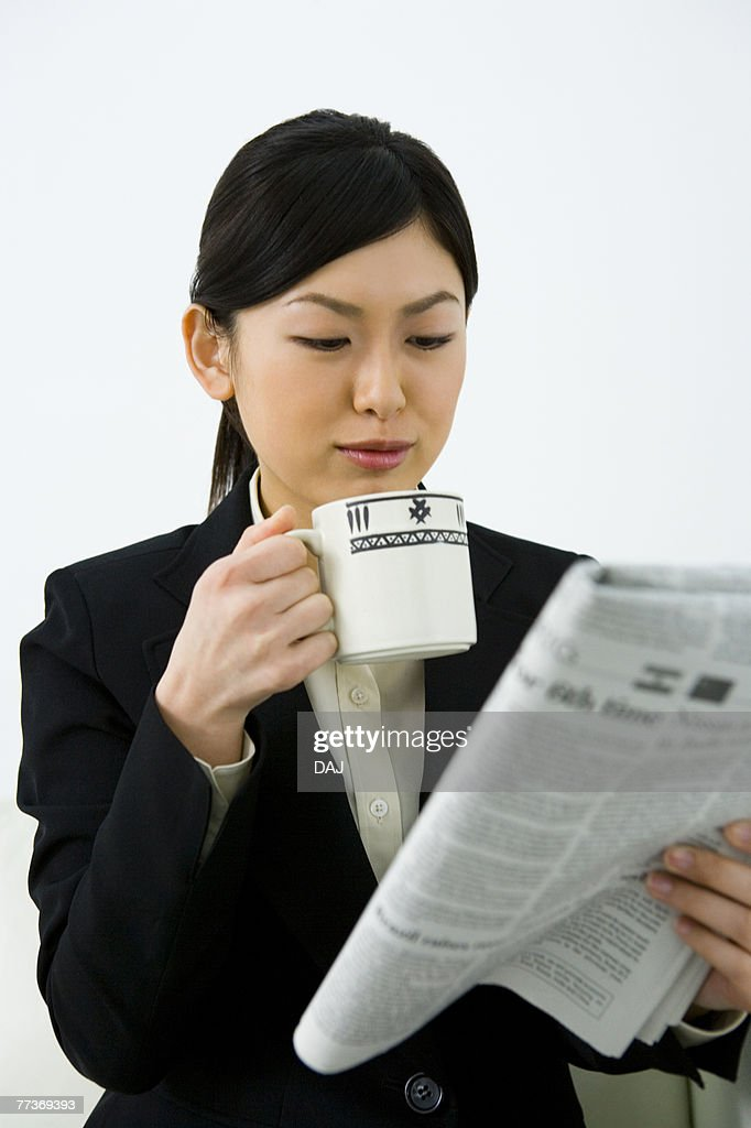 Businesswoman Reading English Newspaper With Holding a Cup, Differential Focus, Waist Up, Front View : Photo
