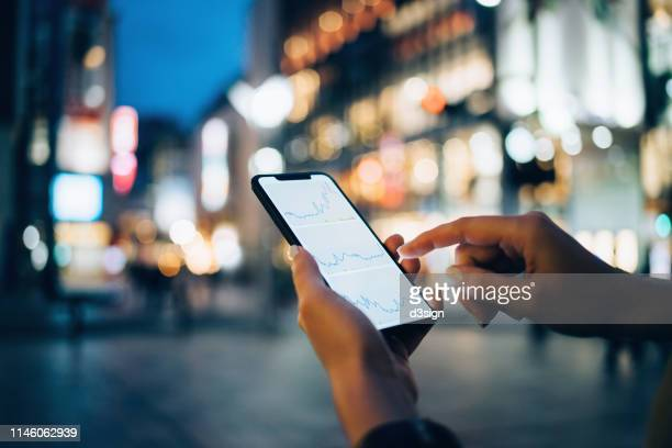 businesswoman reading financial trading data on smartphone in downtown city street against illuminated urban skyscrapers - finanzen stock-fotos und bilder