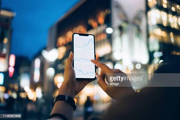 businesswoman reading financial trading data on smartphone in downtown city street against illuminated urban skyscrapers - comercializando - fotografias e filmes do acervo
