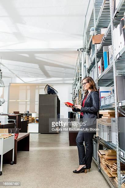 Businesswoman reading folder in office
